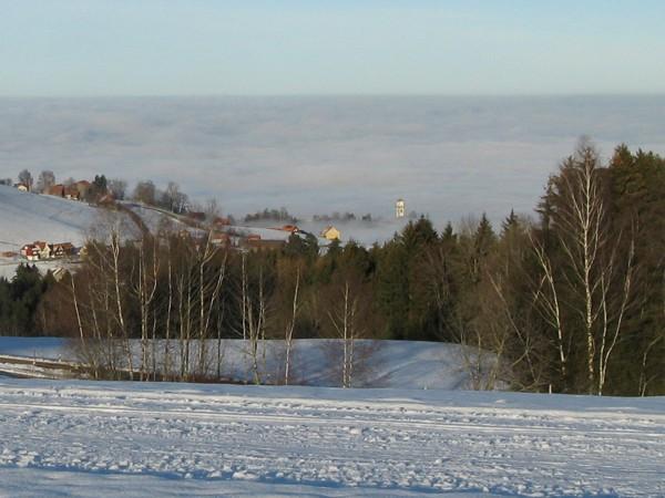 151-Kirchenturm ragt aus dem Nebel